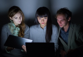 Group of people looking at laptop screen in dark room (© chombosan / Fotolia.com)